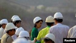 缅甸民主派领袖昂山素季在沙伦基镇与失去土地的村民会面之后观察铜矿。(2013年3月14日资料照)