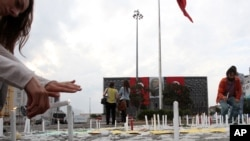 人们在塔克西姆广场点燃蜡烛,悼念那些示威中的死难者