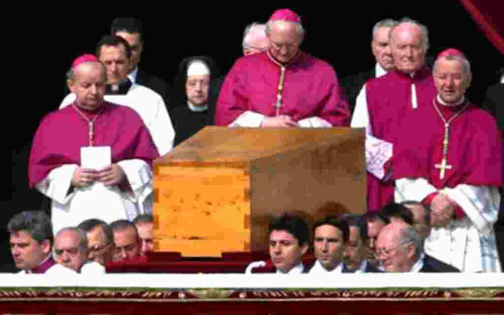 El sacerdote estadounidense James Harvey, reza frente al ataúd de el Papa Juan Pablo II durante la ceremonia de su funeral (2005).