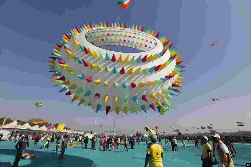 Indians watch a huge kite fly during International kite festival in Ahmadabad,