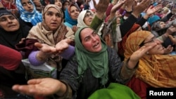 FILE - Kashmiri Muslims women react upon seeing a relic believed to be hair from the beard of Prophet Mohammed, being displayed on the Friday following the festival of Eid-e-Milad-ul-Nabi at Hazratbal shrine in Srinagar, India, Jan.1, 2016.