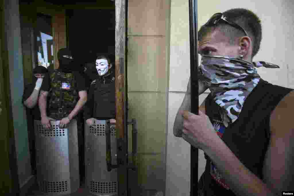 Pro-Russian activists block the entrance to a television station in Donetsk, eastern Ukraine, April 27, 2014.