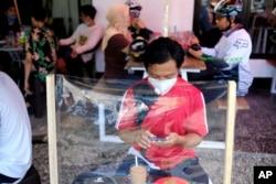 Seorang pria di sebuah warung kopi duduk di meja yang dibatasi pelindung plastik untuk mencegah penularan virus corona, di Makassar, Sulawesi Selatan, 31 Mei 2020. (Foto: AP)