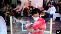 Seorang pria memeriksa telepon genggamnya di sebuah kedai kopi, duduk di belakang pelindung lembaran plastik yang dipasang untuk membantu mengendalikan wabah corona di Makassar, Sulawesi Selatan, Minggu, 31 Mei 2020. (AP Foto / Masyudi S. Firmansyah )