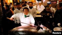 Kiyoshi Kimura (tengah), pemilik jaringan resto sushi di Jepang berpose bersama seekor ikan tuna seberat 230 kg.