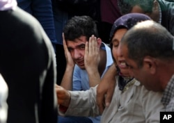 Relatives of people wounded in the explosions in Ankara, react as they wait news for their loved ones outside a hospital, Oct. 10, 2015.