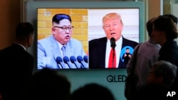FILE - People watch a TV screen showing file footage of U.S. President Donald Trump, right, and North Korean leader Kim Jong Un during a news program at the Seoul Railway Station in Seoul, South Korea, April 21, 2018.