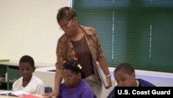 Guru kelas empat Minyon Cantey sedang mengajar David Burrell, 9, kiri, Shalise Allison, 11, tengah, dan Jeffrey Barham, 11, pelajaran seni berbahasa dalam program sekolah musim panas di SD Arlington di Baltimore, Negarabagian Maryland (foto: Dok).