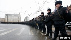 Riot police stand guard during a march to commemorate Kremlin critic Boris Nemtsov, who was shot dead on Friday night, in central Moscow March 1, 2015. Opposition supporters march through Moscow on March 1 in memory of Nemtsov, whose murder has increased