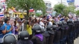 Thai anti government protesters rally next to riot policemen during the registration of constituency candidates in Nakhon Si Thammarat, Dec. 28, 2013.