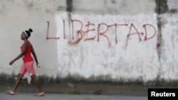 "FILE - A young woman walks near graffiti that reads ""Freedom"" in Havana, Feb. 21, 2016."
