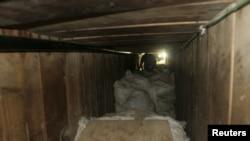 Seorang wartawan harus merangkak untuk memasuki terowongan lintas perbatasan di sebuah gudang di Tijuana (12/7). Pemerintah Meksiko telah menyita lebih dari 40 ton ganja dari dalam terowongan sepanjang 350 meter menuju San Diego, California ini.