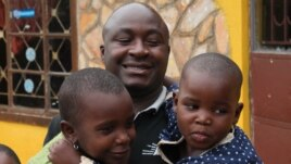 Bosco Segawa with two of the former street kids at his orphanage in Kampala, Uganda, Oct. 25, 2013. (VOA/Hilary Heuler))