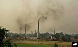 FILE - Smoke rises from chimneys of brick kilns on the outskirts of New Delhi, India, June 16, 2015.