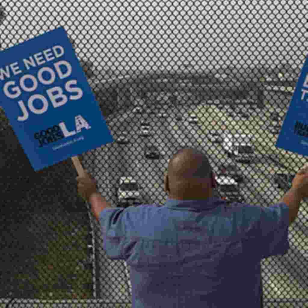 """Christian Del Cid, un residente de la ciudad de Los Ángeles, California muestra letreros con el eslogan """"necesitamos buenos trabajos"""". El estado tiene una de las deudas públicas más altas en Estados Unidos."""