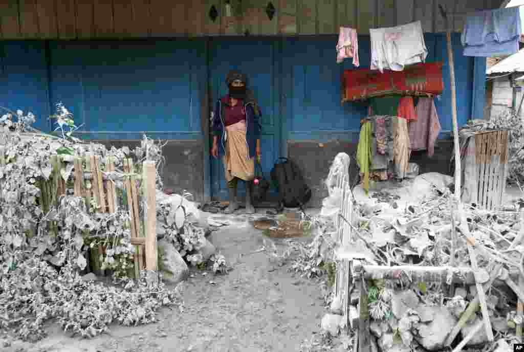 A woman stands outside her house as her front yard is covered with volcanic ash from the eruption of Mount Sinabung, in Mardingding, North Sumatra, Indonesia. The 2,600-meter (8,530-foot) -high volcano has been erupting since Sunday, unleashing volcanic ash high into the sky and forcing the evacuation of villagers living around its slopes.