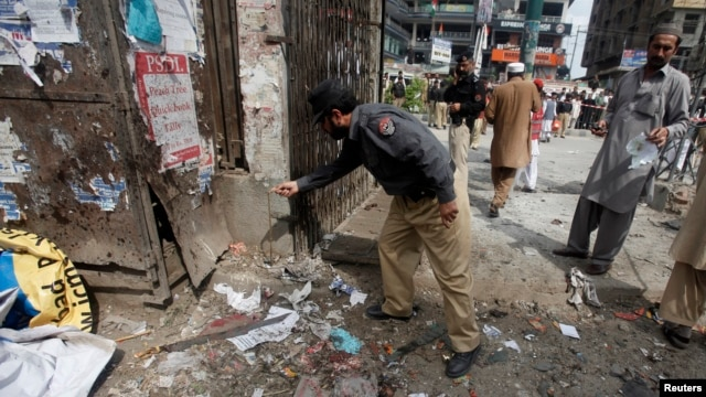 A police officer collects evidence from the site of a bomb blast on University Road in Peshawar, Apr.  29, 2013.