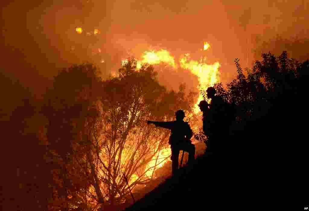 Seorang petugas pemadam kebakaran berusaha memadamkan kebakaran hutan di Lembah Simi, California, AS.