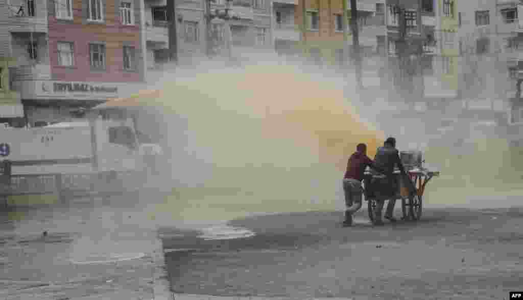 Two men with a tea wagon try to escape from the water cannon used by Turkish police against protesters during a demonstration against government-imposed curfews on areas of eastern Turkey, in Diyarbakir, southeastern Turkey.