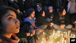 Young people gather around candles as they begin three days of mourning Friday to mourn dozens who died in the protests that drove their autocratic leader from power, in Tunis, January 22, 2011