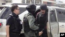 布特(右)周二在泰国警察的押解下抵达曼谷机场