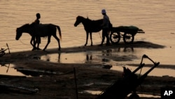 In this photo taken, Saturday, April 3, 2010, Cambodian men take their horses for washing in the Mekong river bank near Khporp village, Kandal province about 22 kilometers (14 miles) north of Phnom Penh, Cambodia.