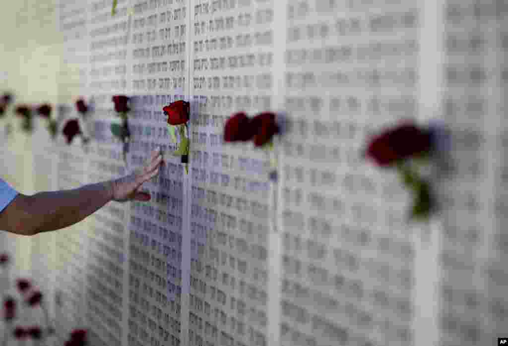 A veteran touches the wall of names at the Armored Corps memorial for fallen soldiers after a ceremony marking the annual Memorial Day for those killed in more than a century of conflict between Jews and Arabs, in Latrun near Jerusalem.