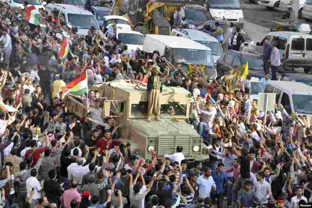 A convoy of peshmerga vehicles is escorted by Turkish Kurds on their way to the Turkish-Syrian border, in Kiziltepe near the southeastern city of Mardin. Iraqi peshmerga fighters arrived in southeastern Turkey en route for the Syrian town of Kobani to try to help fellow Kurds break an Islamic State siege which has defied U.S.-led air strikes.