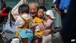 An elderly man plays with children near a commercial office building in Beijing on May 10, 2021. (AP Photo/Andy Wong)