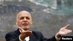 FILE - Afghan President Ashraf Ghani speaks during a news conference in Kabul, Afghanistan, July 15, 2018. He telephoned neighboring Pakistan's would-be prime minister, Imran Khan, to congratulate him on his election victory and invited him to visit Kabul.