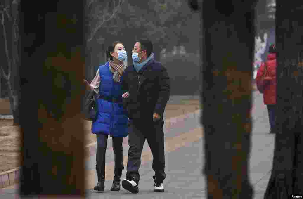 A couple wearing face masks walk along a street on a hazy afternoon in Beijing, China.