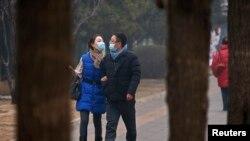 在雾气笼罩的下午,一对相爱男女戴口罩走在北京街头。(2014年2月24日)