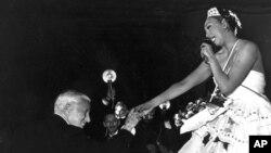 """Charlie Chaplin félicite l'artiste Joséphine Baker après sa prestation au gala de charité """"Le Bal des Petits Lits Blancs"""", au Moulin Rouge à Paris, le 20 mai 1953."""