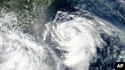 Gambar satelit yang dirilis oleh NASA menunjukkan Topan Hagupit mendekati Taiwan, tengah kiri, Minggu, 2 Agustus 2020.