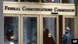 FILE - A person with a smart phone enters the Federal Communications Commission (FCC) in Washington, Dec. 14, 2017.