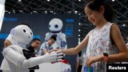 2018年7月4日,上海2018中國國際機器人展覽會上,一位訪客與機器人握手。
