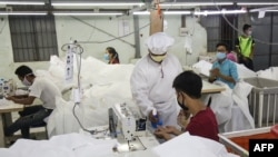 This photo taken on May 8, 2020 shows workers wearing face masks sewing disposable surgical gowns for health workers as protection from the COVID-19 coronavirus at a garment factory in Yangon. - The factory which has switched from making clothes for expor