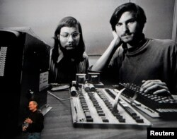 """FILE - Apple Chief Executive Officer Steve Jobs stands beneath a photograph of him and Apple-co founder Steve Wozniak from the early days of Apple during the launch of Apple's new """"iPad"""" tablet computing device in San Francisco, California, Jan. 27, 2010."""