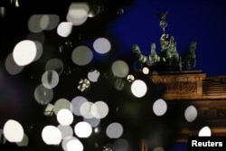 A Christmas tree is illuminated in front of Brandenburg Gate in Berlin, Germany, November 26, 2020. REUTERS/Hannibal Hanschke TPX IMAGES OF THE DAY