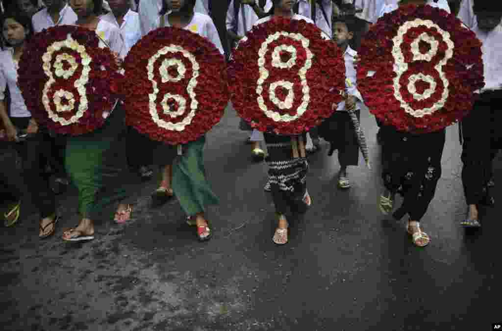 Những sinh viên Miến Điện thuộc thế hệ 88 nổi bật cầm vòng hoa tượng trưng trong một cuộc tuần hành ở trung tâm thành phố Rangoon, 8 tháng 8, 2013.