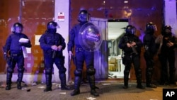 FILE - Riot police take position in front of a vacant bank occupied by squatters in Barcelona, Spain.