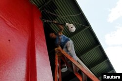 "Cuban migrant Barbaro Rodriguez, 43, who ran out of money, works painting a private business in Paso Canoas, Panama, March 22, 2016. ""I am presently earning $20 a day painting this building. Hopefully, I can make enough money to continue our journey"" to the U.S., he says."