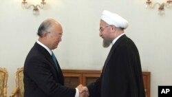Presiden Iran Hassan Rouhani, kanan, berjabat tangan dengan Kepala Badan Nuklir PBB, Yukiya Amano di Teheran, 17 Agustus 2014. (Foto: dok.)