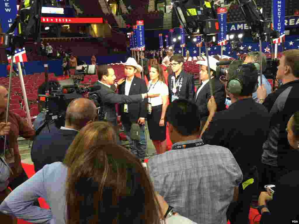 Four Hispanic delegates -- two from Texas, wearing hats, and two from Florida -- are interviewed by TV Telemundo on the floor at the Republican National Convention at Quicken Loans Arena, in Cleveland, July 19, 2016. (Photo: Mia Bush / VOA)