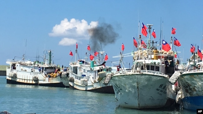 Taiwanese fishing boats flying national flags prepare to leave for Taiping Island in 2016. Taiwan and China have disputing claims in the South China Sea.