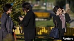 지난 10월 평양 보통강 백화점 인근 공원에서 휴식을 즐기는 여성들 중 한 명이 손전화를 사용하고 있다.