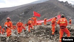 中國軍人,武警和官員組成的救援隊疏散村民搶救泥石流受=難者。(2013年3月30日資料照片)