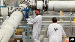 """En esta foto de archivo del 9 de julio de 2014, los trabajadores que usan ropa protectora y calzado inspeccionan una válvula en la granja de tanques """"C"""" en la Reserva Nuclear de Hanford, cerca de Richland, Wash."""