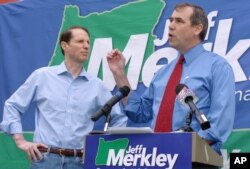 FILE - Jeff Merkley, then a Democratic candidate for the U.S. Senate, right, speaks at a rally with Oregon Sen. Ron Wyden, in Portland, May 31, 2008.