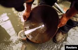 Seorang penambang menggunakan air dan merkuri untuk mengekstraksi emas dari batu yang dikumpulkan dari tambang emas. (Foto: ilustrasi).